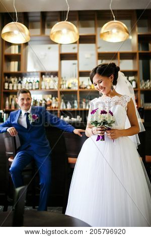 Newlyweds at the bar scene, the bride laughs cheerfully, the groom sits on a bar stool, good lighting.