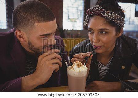Young friends enjoying milkshake at cafe