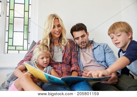 Family With Children Sitting On Bed Reading Book Together