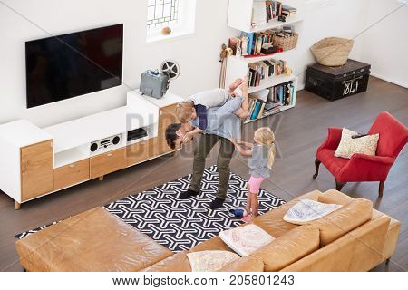 Overhead Shot Of Father Playing With Children In Lounge