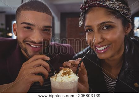 Portrait of happy young friends enjoying milkshake in cafe
