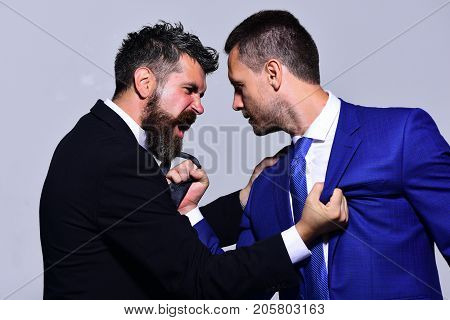Coworkers decide upon best working position. Businessmen with angry faces in formal suits on grey background. Company leaders fight for business leadership. Business opposition and competition concept