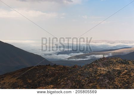 hiker the winner stands on the edge of the rock with sticks raised up in front of the valley covered by clouds in the Caucasus. The concept of motivation to achieve goals and win over circumstances