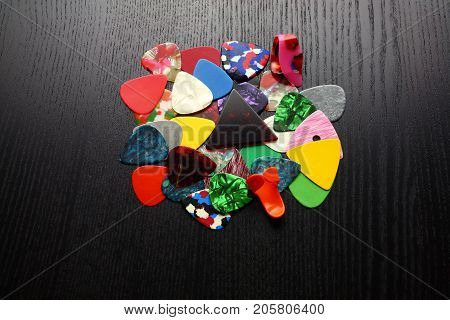 Pile of Guitar Plectrums on Wooden Background