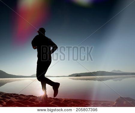 Leakage Of Light In The Lens. Exercising Man Silhouette Against To Morning Sun.