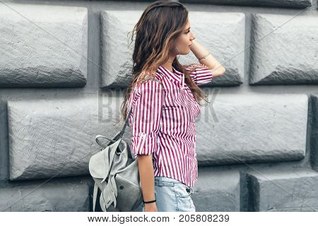 Fashion model wearing red striped shirt and backpack posing in the city street. Fashion urban outfit. Casual everyday clothing style.