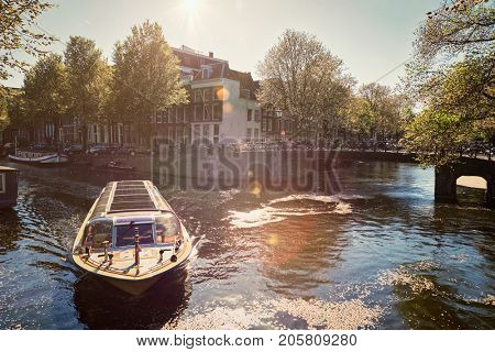 Amsterdam canal with tourist boat and old houses on sunset. Amsterda, Netherlands