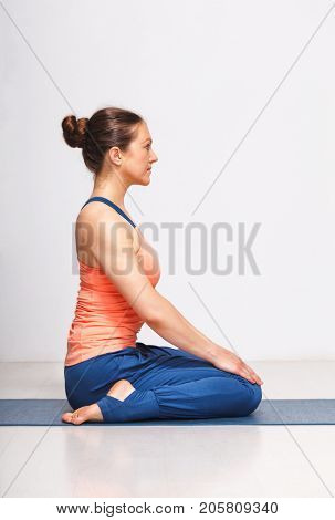 Woman in Hatha yoga asana Vajrasana - vajra pose or diamond pose on yoga mat on yoga mat in studio on grey bagckground