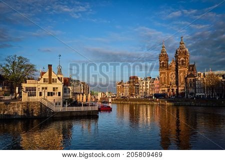 Amsterdam canal and Church of Saint Nicholas (Sint-Nicolaaskerk) on sunset. View from Amsterdam Centraal. Amsterdam, Netherlands