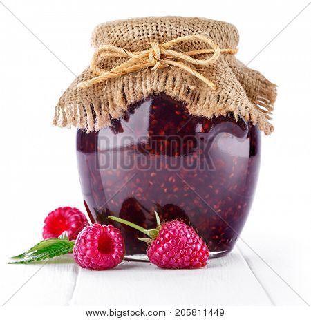 Raspberry confiture in can with fresh berries and leaf on white wooden board, isolated background.