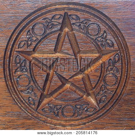 Pentacle with patterned surround carved in a dark wooden block