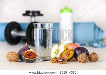 Healthy lifestyle concept. Diet and fitness. Healthy lifestyle style. Water and fruit as a healthy food on a background of blurry fitness equipment. Proper nutrition and active healthy lifestyle.