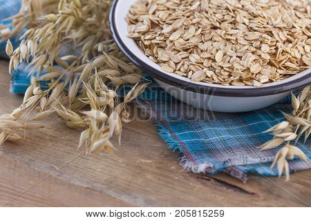 old fashioned rolled oats in a bowl on wooden table - diet and breakfast