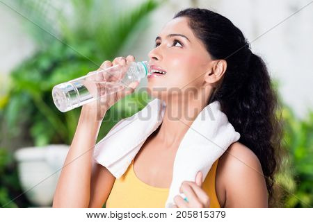 Portrait of healthy young woman drinking plain water during workout outdoors