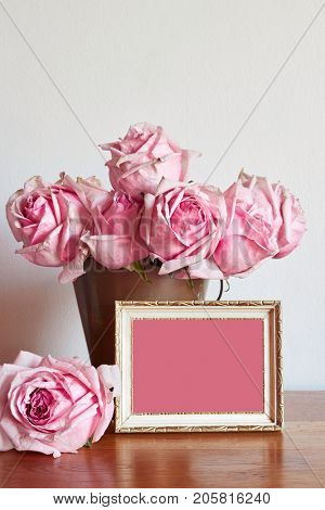A bunch of blush pink roses in an antique brass bucket. Gold and white rustic frame. Shabby chic against neutral painted wall. Space for text