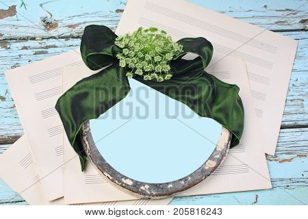 Damaged antique round frame with emerald green silk ribbon. Top view on damaged painted wood table and music paper. Space for text