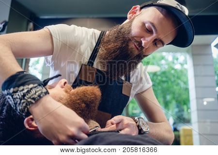 Side view headshot of a redhead bearded young man smiling, ready for shaving in the hair salon of a skilled barber with a classic straight razor in his hand