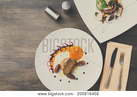 Roasted goose liver with date and apple, fruit and berry sauce painting with cutlery and seafood salad top view. Creative french cuisine, delicatessen restaurant meal