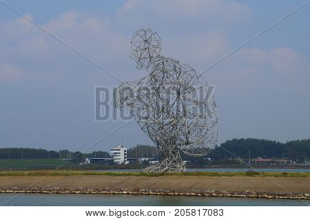 Lelystad, Netherlands - September 24, 2017: Antony Gormley's metal statue of a man sitting on his heels, also known as The Shitting Man, on an enclosure dam in Batavia Haven in the city of Lelystad.
