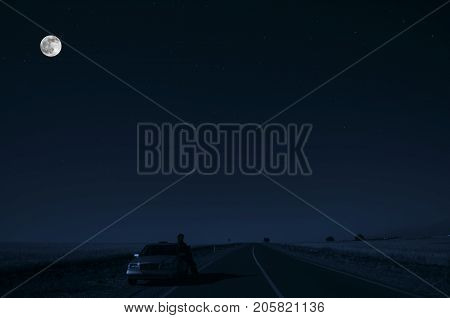 Road With Car And Sillhouette Of Man And A Car At The Road Side At Night Under Moon Light. Azerbaija