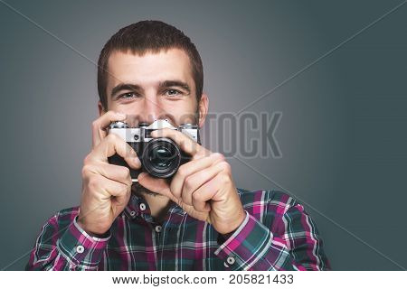 Hipster fashion photographer man holding retro camera Toned
