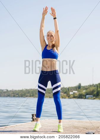 Gorgeous, cheerful, positive sports girl with a blonde ponytail, doing fitness training on a blurred river background. Copy space.