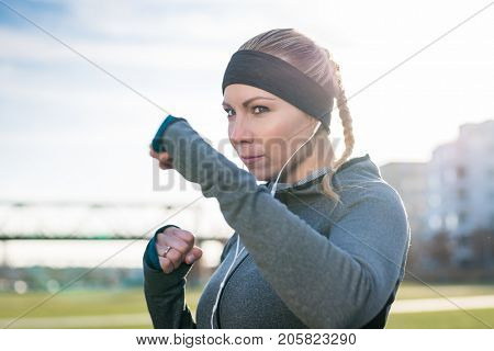 Portrait of a strong young woman practicing boxing exercise while looking forward with confidence and determination outdoors in the city
