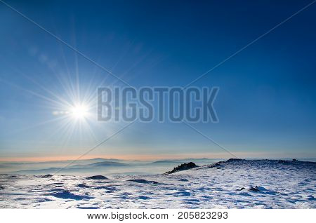 Winter landscape with a raising sun and sun rays against a clear blue sky, wintry background