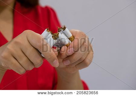 Quit Smoking. Closeup Of Beautiful Happy Female Breaking Cigarette. Portrait Of Smiling Woman Holdin