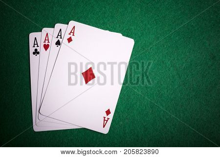 Four aces on green poker table
