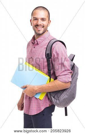 Young smiling student holding textbooks on white background