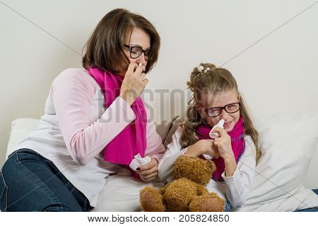 Sick mother and daughter. A woman and a child with a runny nose they sneeze use a handkerchief.