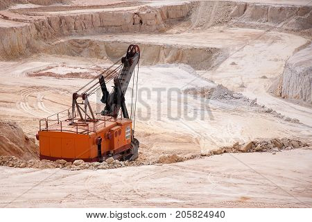 Excavator digging out raw materials in opencast mine