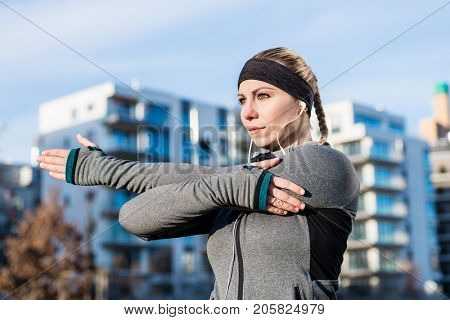 Portrait of a determined young woman stretching her left arm during warm-up routine before outdoor workout in a sunny day