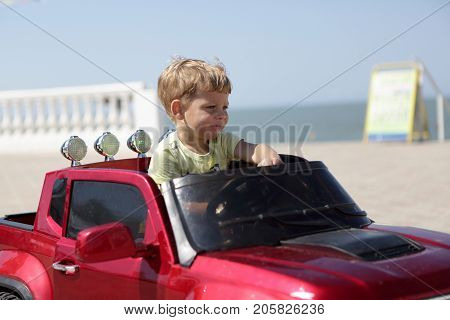 Child Driving Red Car