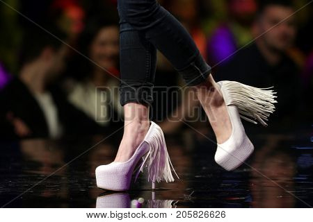 Sofia, Bulgaria - 23, March 2017: A model walks the runway in stylish pink shoes during a Fashion Show. Fashion catwalk event showing new collection of clothes. Legs and shoes only.