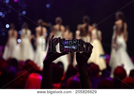 Sofia, Bulgaria - 23, March 2017: A woman from the audience takes picture with her phone during a Fashion Show. Fashion catwalk event showing new collection of clothes.