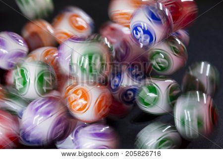 Sofia, Bulgaria - 24, November 2016: Colourful lottery balls in a bingo machine. Lottery balls in a sphere in motion. Gambling machine and euqipment. Blurred lottery balls in a lotto machine.