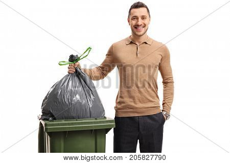 Young man throwing out the garbage and smiling isolated on white background