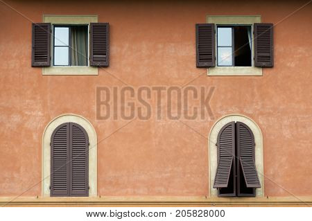 Arched and square windows with wooden shutters on facade of Tuscany house