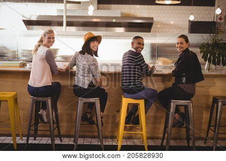 Rear view portrait of smiling young friends sitting on stools at counter in coffee shop