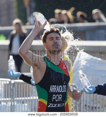 STOCKHOLM - AUG 26 2017: Running triathlete Miguel Arraiolos (POR) splashing water from a bottle in his face in the Men's ITU World Triathlon series event August 26 2017 in Stockholm Sweden