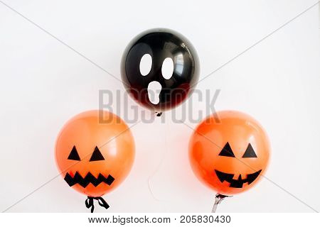 Halloween minimal concept. Three balloons with funny smiling and scary faces on white background. Flat lay top view.