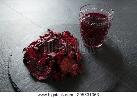 Juice glass with beetroot on plate over slate
