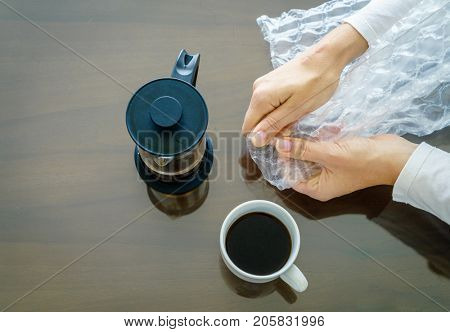 Close-up image of woman's hands popping bubble wrap. View from above