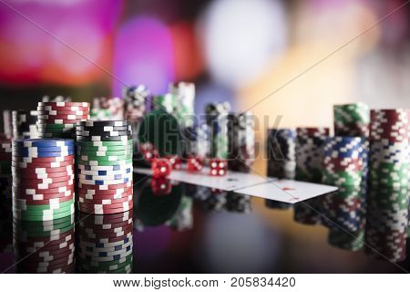 Casino concept. Cadrs, chips and dice on colorful bokeh.