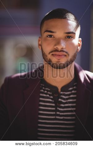 Portrait of confident young man wearing maroon blazer at coffee shop