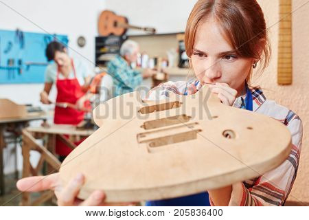 Guitar maker apprentice builds new guitar with wood