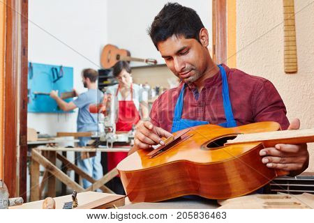 Trainee of guitar maker repairs guitar at luthier's shop