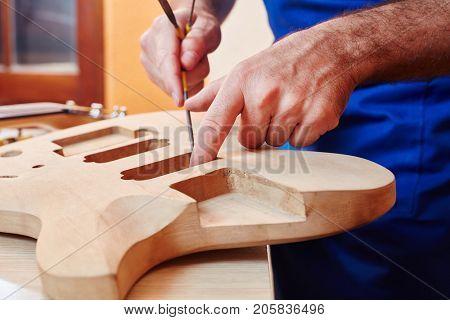 Guitar maker works on handmade guitar at carpenter's workshop